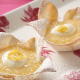 orange-and-lemon-curd-tarts-in-mountain-bread-base-served-with-a-dollop-of-cream-and-dusted-with-icing-sugar.